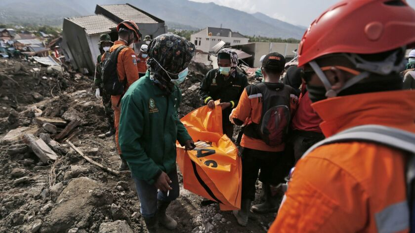 Workers carry a body bag containing the remains of an earthquake victim recovered from under rubble in the city of Palu on the Indonesian island of Suwalesi on Thursday.
