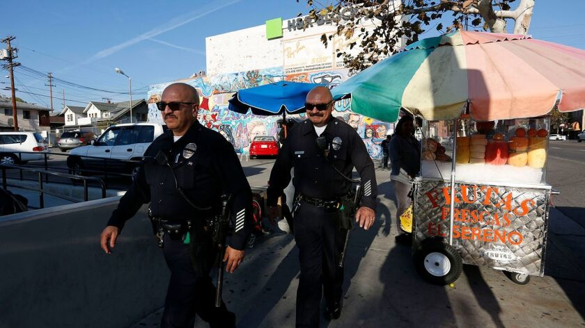 Veteran L.A. police Officer J.C. Duarte, left, on patrol with partner Harold Marinelli, says adding federal immigration enforcement to peace officers' to-do list will just drive a wedge between immigrants and law enforcement.