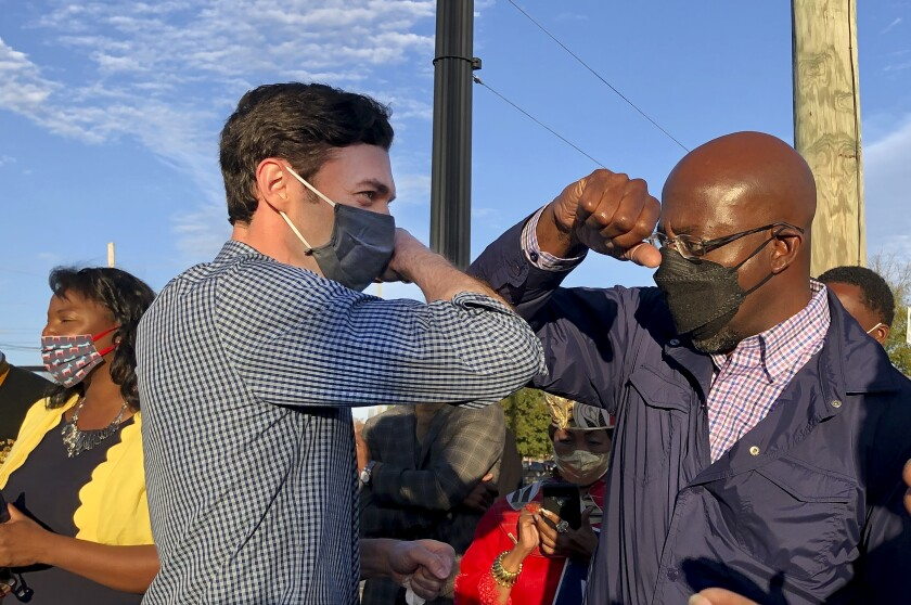 Democrats Jon Ossoff and Raphael Warnock tap elbows during a joint campaign rally on Nov. 15, 2020, in Marietta, Ga.