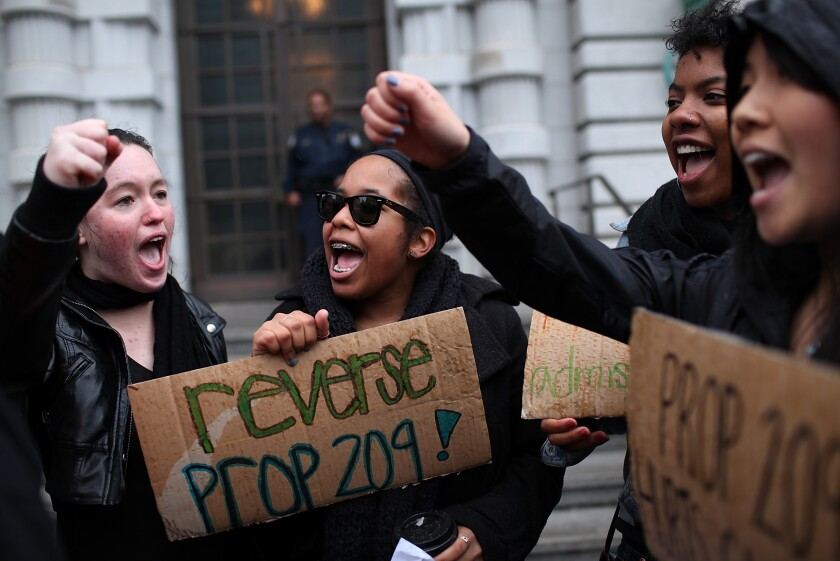 Students hoping for a repeal of California's Proposition 209 hold signs as they protest.