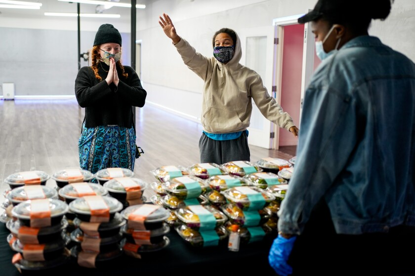 Caroline Diamond, left, and Kaileigh Williams of North Hollywood thank JaQuel Knight and volunteers during a meal giveaway event put on by Knight and Everytable at KreativMndz Dance Academy in Burbank.