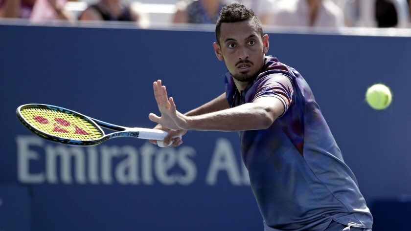 Nick Kyrgios, of Australia, returns a shot from John Millman, of Australia, during the first round o