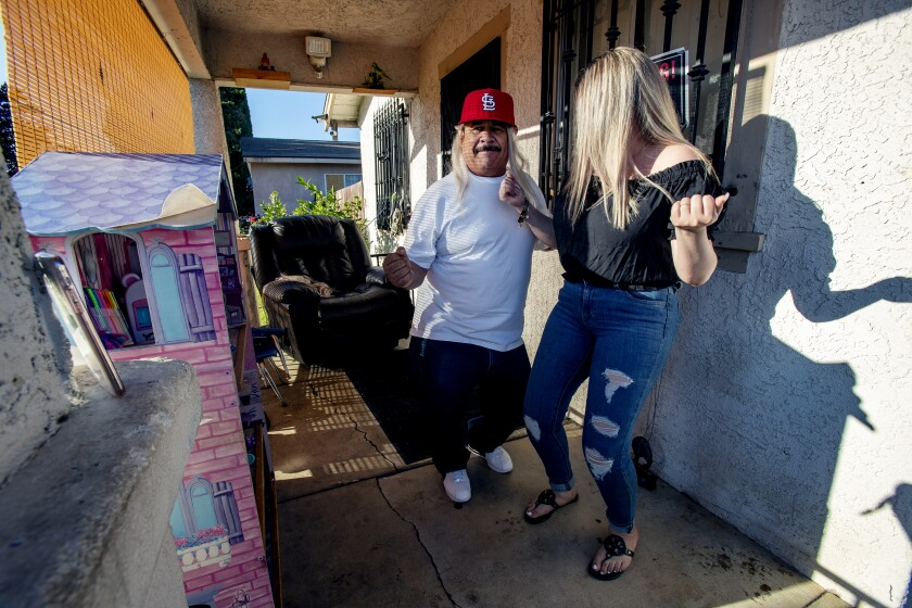 Genaro Rangel wears a wig while dancing with his daughter Wendy to Latin music during a TikTok film session.