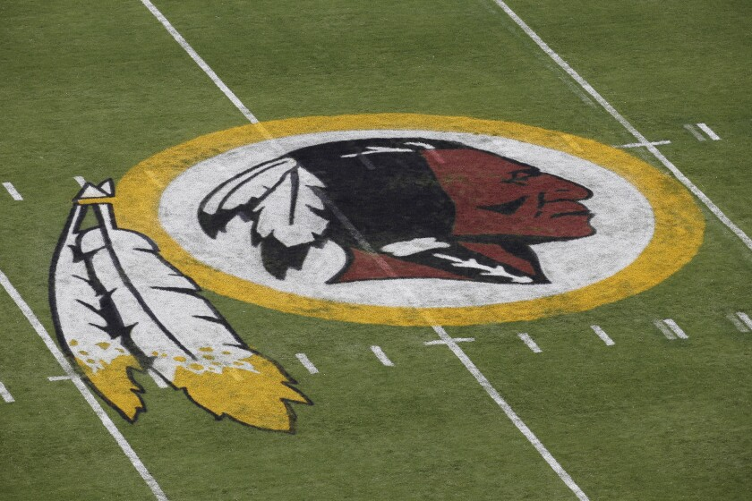 "FILE - In this Aug. 7, 2014 file photo, the Washington Redskins NFL football team logo is seen on the field before an NFL football preseason game against the New England Patriots in Landover, Md. The recent national conversation about racism has renewed calls for the Washington Redskins to change their name. D.C. mayor Muriel Bowser called the name an ""obstacle"" to the team building its stadium and headquarters in the District, but owner Dan Snyder over the years has shown no indications he'd consider it. (AP Photo/Alex Brandon, File)"