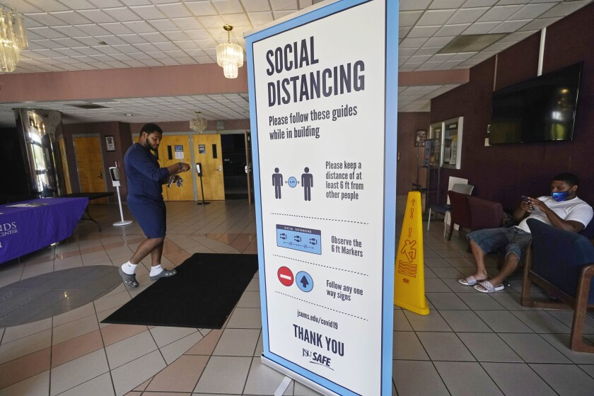 FILE — In this July 27, 2021 file photo, social distancing as well as face covering is recommended at the COVID-19 vaccination site in the Rose E. McCoy Auditorium on the Jackson State University campus in Jackson, Miss. Hundreds of colleges nationwide have told students they must be fully vaccinated against COVID-19 before classes begin in a matter of weeks. (AP Photo/Rogelio V. Solis, File)