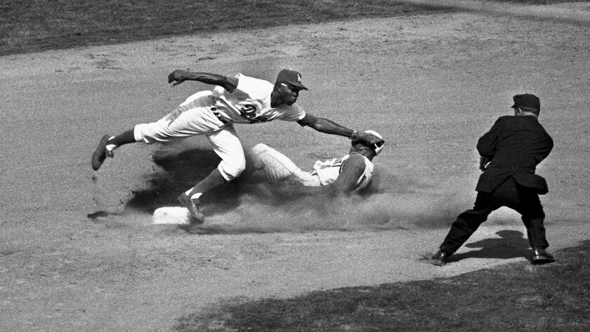 Dodger's Jim Gilliam makes a tag as Cincinnati Reds' Tommy Harper slides safely into second during the sixth inning.