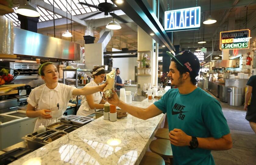 Chef Sarah Hymanson, left, hands a falafel sandwich to customer Ryan Badaraco at Kismet Falafel, previously Madcapra.
