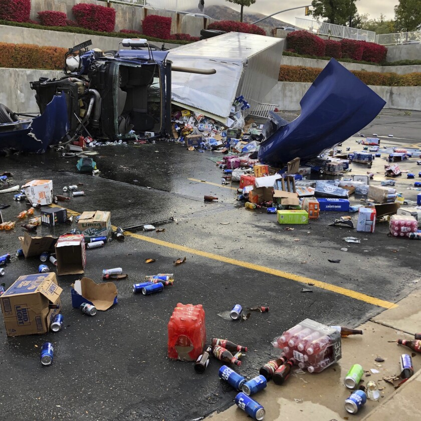 A semi-trailer driver, hauling beer, suffered serious injuries after his vehicle rolled over and crashed in a parking lot of a church, Thursday morning, Oct. 10, 2019, in Sandy Utah. Cans of beer have littered the parking lot of a church of The Church of Jesus Christ of Latter-day Saints in a Salt Lake City suburb after a semi-trailer crashed that was carrying cases of brew banned by the faith.(Derek Petersen/KSL-TV - The Deseret News via AP)
