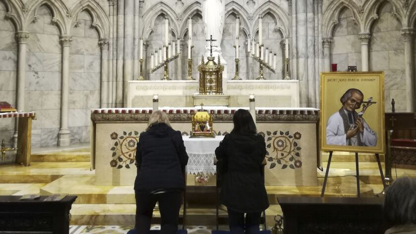 Two women pray in front a container bearing the 150-year-old heart of French priest St. John Vianney on Saturday at St. Patrick's Cathedral in New York. The heart is being toured throughout the United States.