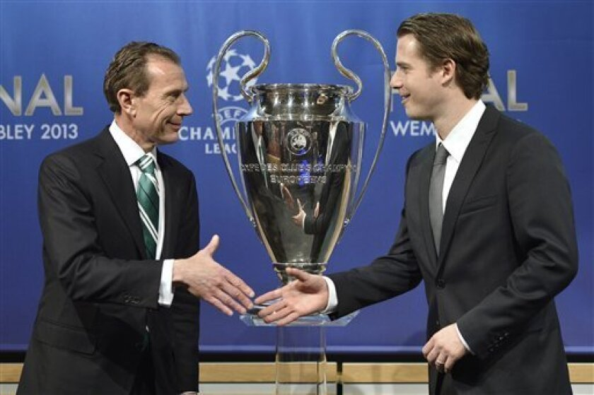 Real Madrid CF International Relations Director Emilio Butragueno, left, shakes hands with Borussia Dortmund's former player Lars Ricken, right, during the draw of the games of the UEFA Champions League 2012/13 for the semi-finals and final UEFA headquarters in Nyon, Switzerland, Friday,12 April 20