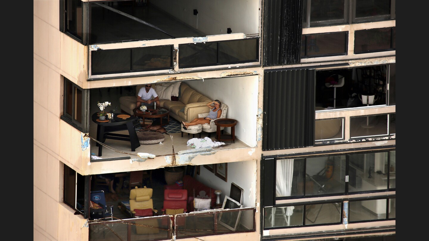 Two people sit in an apartment with a wall missing after Hurricane Maria passed over the island nearly a week ago.