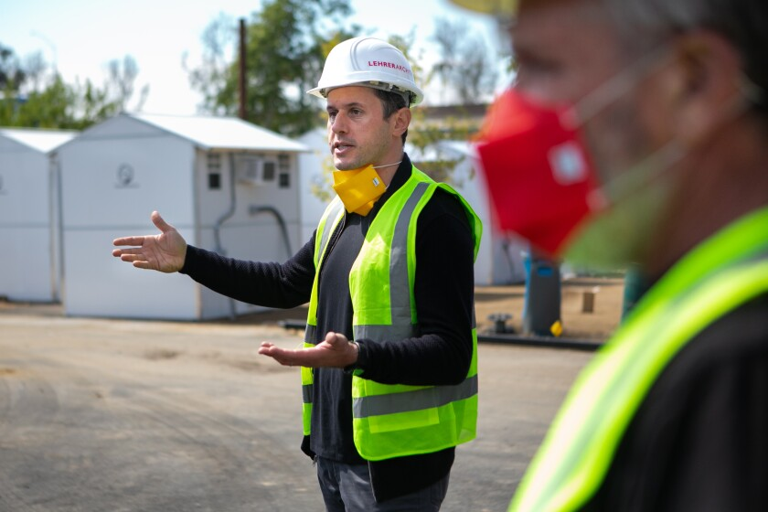 Architect Nerin Kadribegovic in a hard hat and yellow safety vest in the middle of a tiny village that is under construction