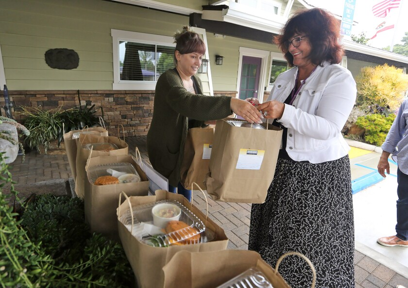 CEO Sue Bright, right, and house chef Fatima Abuzaineh bring in pre-packaged lunches donated by the Tavern House Kitchen + Bar to the New Directions for Women facility in Costa Mesa on Monday.