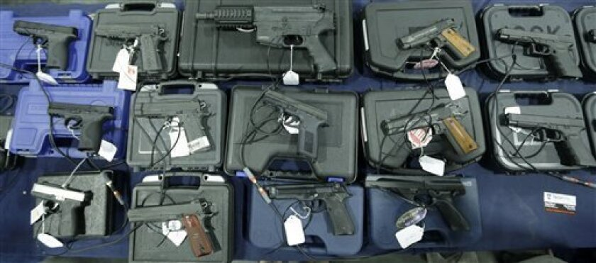 FILE - This March 3, 2013, file photo shows handguns displayed in Sandy, Utah. Democrats pushed an assault weapons ban through a Senate committee on Thursday, March 14, 2013, and toward its likely doom on the Senate floor, after an emotion-laden debate that underscored the deep feelings the issue stokes on both sides (AP Photo/Rick Bowmer, File)