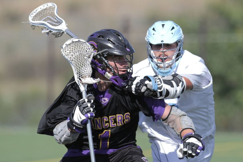 Carlsbad junior Spencer Beyer (left) attacks the net as Pacific Ridge's Ian Torbett defends. Beyer scored three goals for the Lancers, who advanced to the Division I championship.