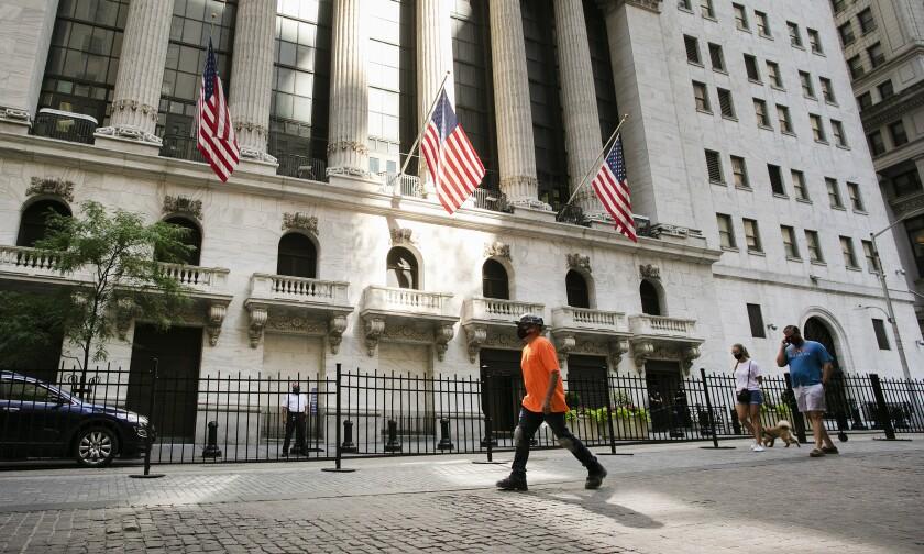Varias personas caminan el martes 21 de julio de 2020 frente a la Bolsa de Valores de Nueva York. (AP Foto/Mark Lennihan)