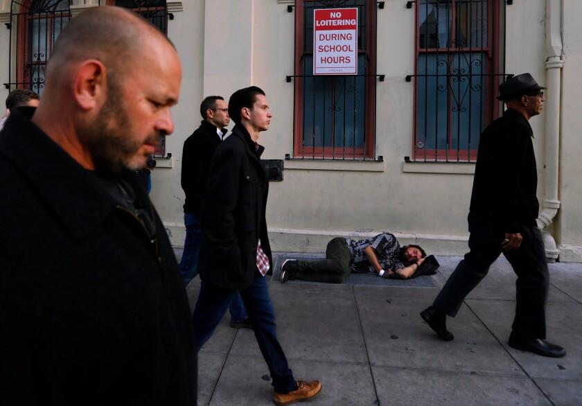 Pedestrians pass a homeless man sleeping on a sidewalk in San Francisco.