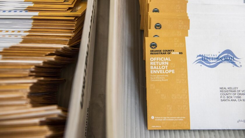Piles of mail-in ballots are readied to be counted at the Orange County Registrar of Voters on Wedne
