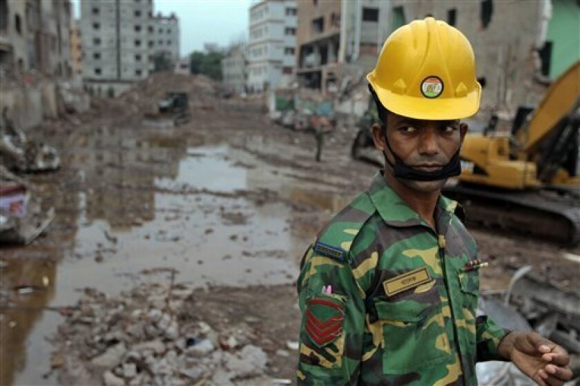A Bangladeshi soldier stands at the site where a Bangladesh garment-factory building collapsed on April 24 in Savar, near Dhaka, Bangladesh, Monday, May 13, 2013.Nearly three weeks after the building collapsed, the search for the dead ended Monday at the site of the worst disaster in the history of the global garment industry. (AP Photo/A.M. Ahad)