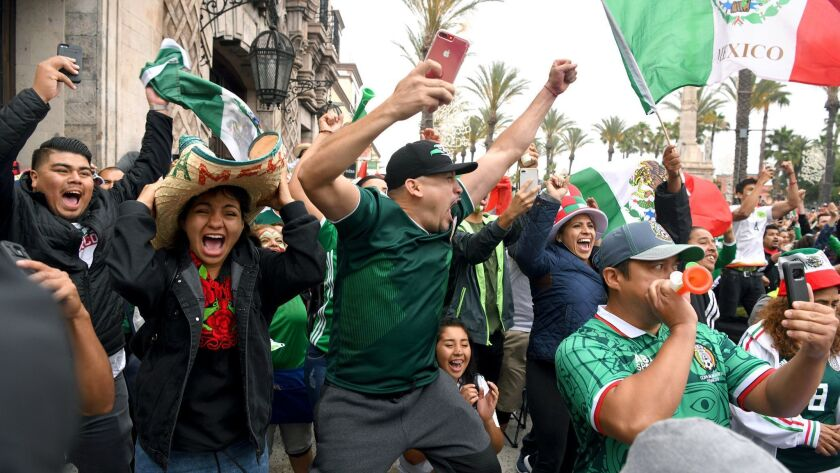 Fans celebrate Mexico's first goal while watching the World Cup match between Mexico and South Korea at Plaza Mexico in Lynwood.