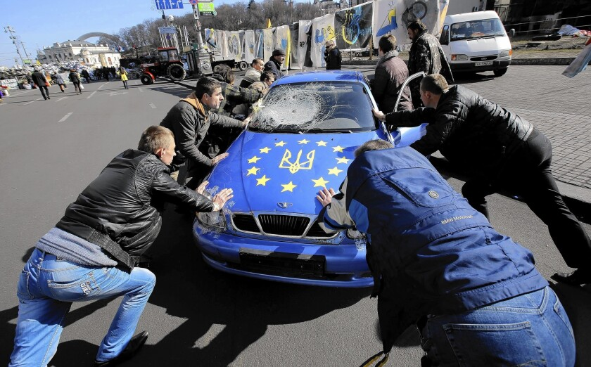 Ukrainian men push a car decorated with symbols of the European Union and Ukraine near Independence Square in Kiev. On Friday, Ukrainian officials sealed a deal deepening political cooperation with the 28-nation European Union.