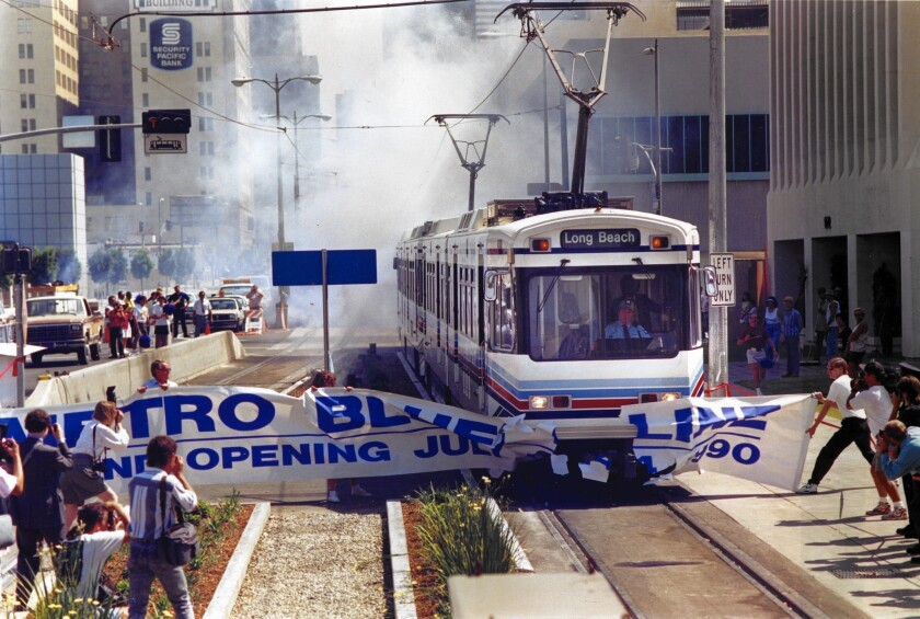 The first Metro Blue Line train rips through an opening-day banner as it makes its way toward the Pico Boulevard station in downtown Los Angeles on July 15, 1990.