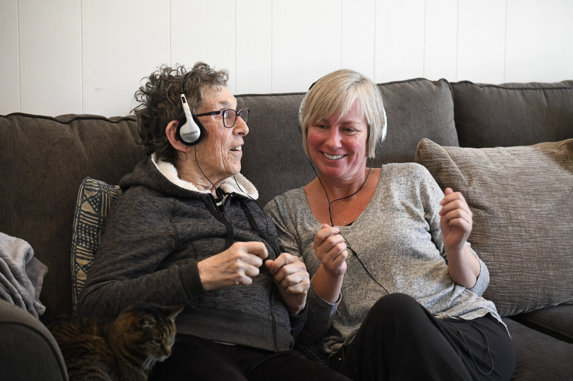 Stacey Skrocki (irght), volunteer with Jewish Family Service, and Gloria Wasserman move to the music as they do in-home Music & Memory therapy.