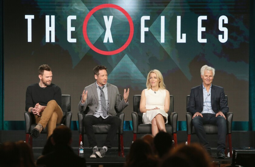"""Actors Joel McHale, David Duchovny, Gillian Anderson and creator/executive producer Chris Carter speak onstage during """"The X-Files"""" panel discussion."""