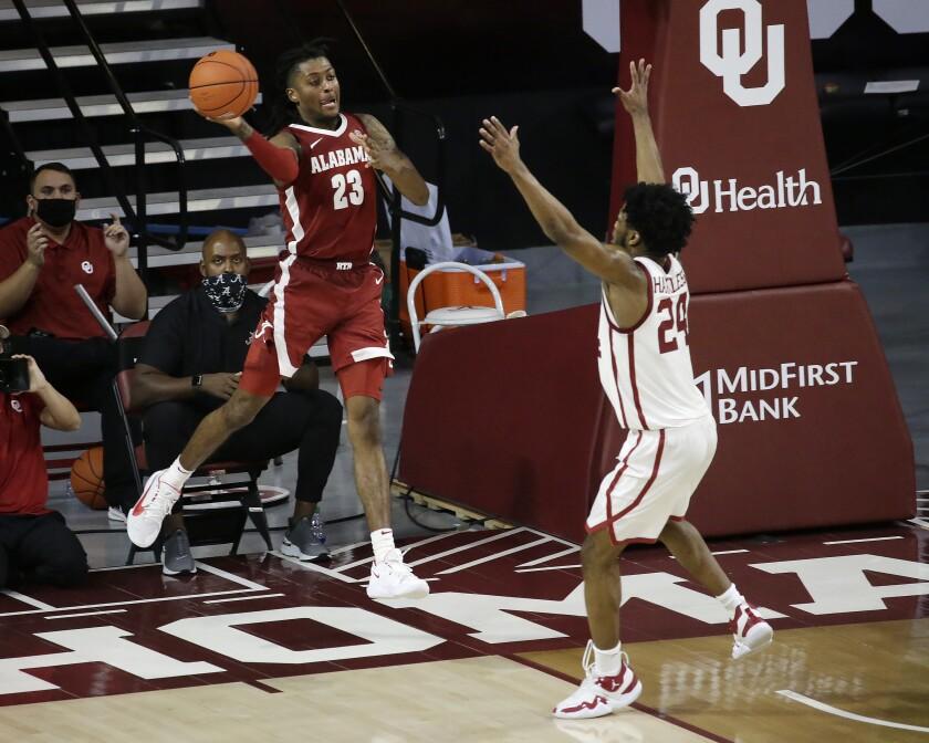 Alabama's John Petty Jr. (23) throws the ball away from Oklahoma's Elijah Harkless (24) during the second half of an NCAA college basketball game in Norman, Okla., Saturday, Jan. 30, 2021. (AP Photo/Garett Fisbeck)
