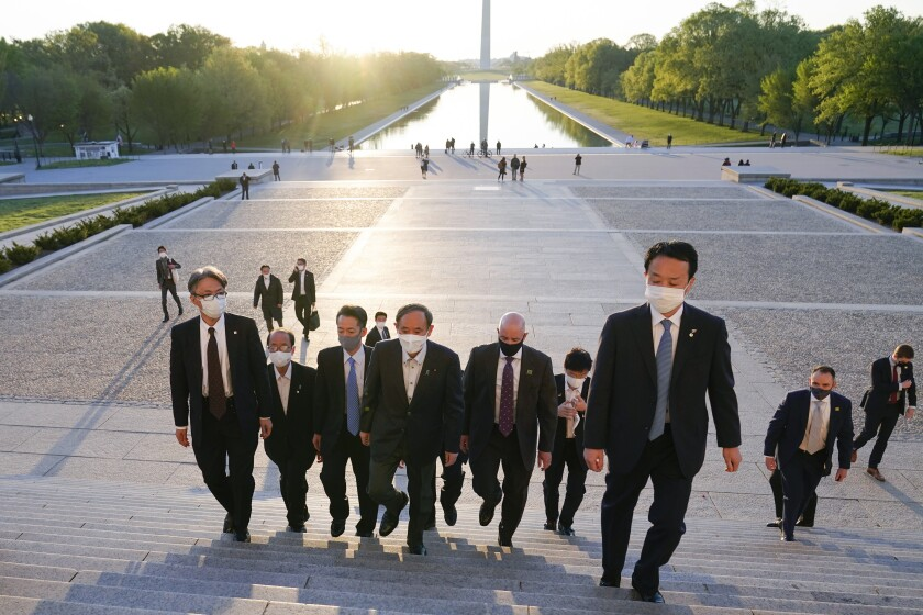 With the Washington Monument in the background, Japanese Prime Minister Yoshihide Suga visits the Lincoln Memorial, Saturday, April 17, 2021, in Washington. (AP Photo/Alex Brandon)