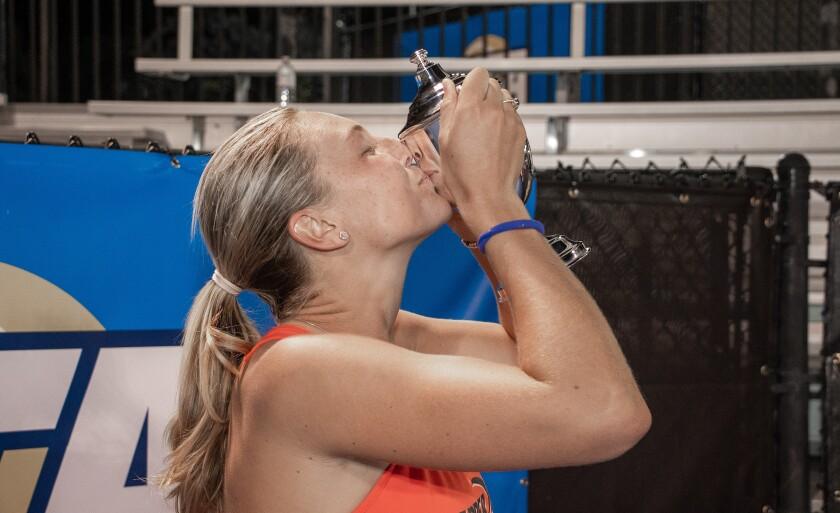 Pepperdine tennis player Ashley Lahey kisses a trophy.