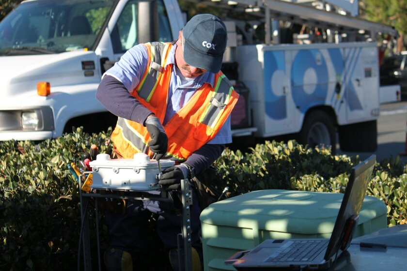 A Cox Communications worker installs  Wi-Fi  equipment.  Internet Service Providers across the country are opening access to their Wi-Fi hotspots to the public and taking other steps to help keep people connected during the coronavirus crisis.