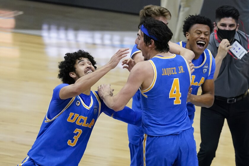 UCLA's Johnny Juzang, left, and Jaime Jaquez Jr. celebrate after the Bruins' Elite 8 win over Michigan in Indianapolis.