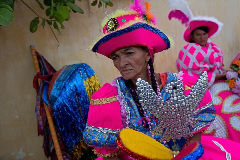 """En esta imagen, mujeres vestidas de """"baianas"""" esperan al inicio del carnaval maracatu, en Nazare da Mata, Brasil. Los bailarines maracatu se reúnen en la plaza principal de la localidad, procedentes de toda la ciudad y de áreas rurales de su entorno. (Foto AP/Eraldo Peres)"""