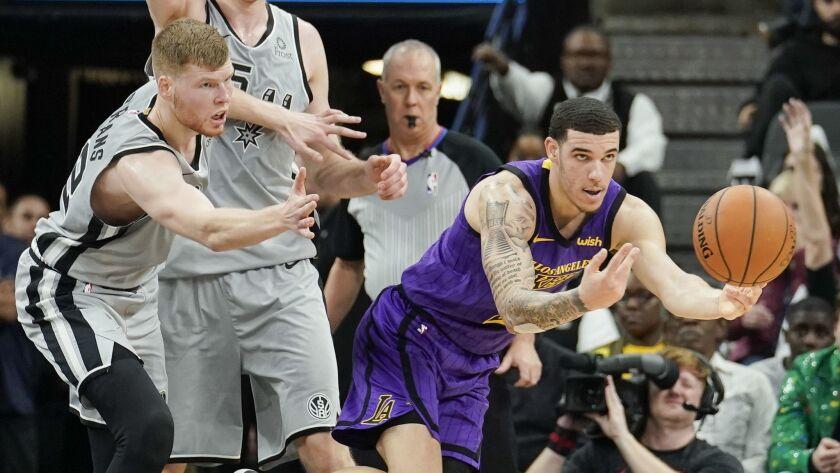 Los Angeles Lakers' Lonzo Ball, right, passes the ball as he evades San Antonio Spurs' Davis Bertans