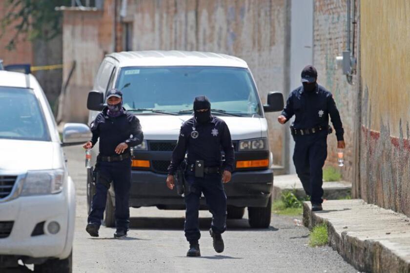 Agente de la Policía Federal mexicana vigilan este jueves las inmediaciones de una finca en la que fueron hallados 10 cadáveres s en una fosa clandestina y unas 9 bolsas de plástico con restos humanos, en la localidad de Tonalá, estado de Jalisco (México). EFE/Francisco Guasco