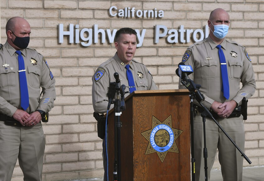 Three highway patrol officers stand at a lectern with the CHP logo in front of microphones
