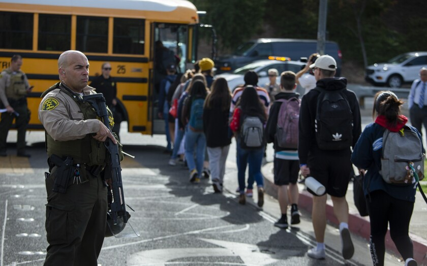 A sheriff's deputy looks on as students board buses after Thursday's deadly shooting at Saugus High School