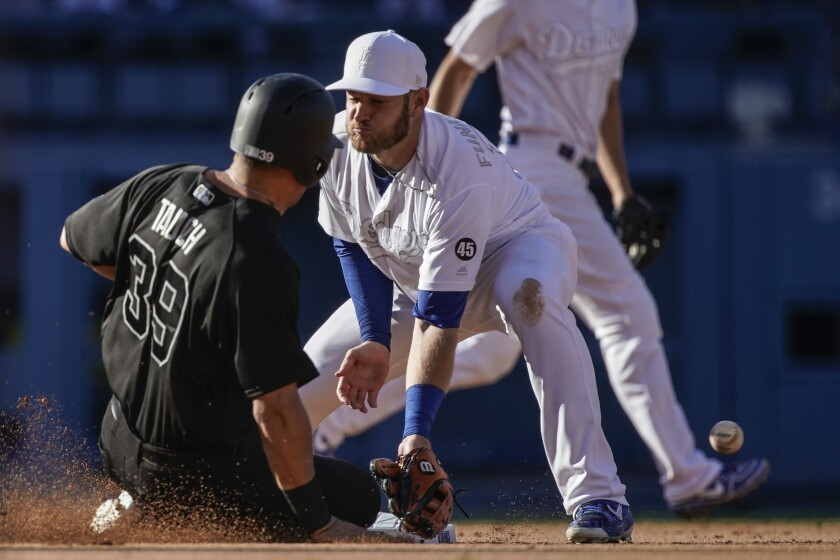 Yankees' Mike Tauchman steals second base in front of Dodgers second baseman Max Muncy.