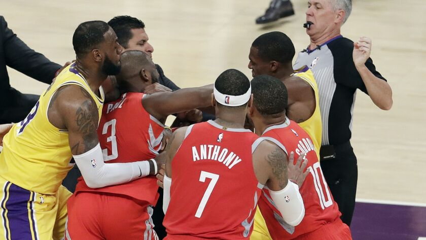 Houston Rockets guard Chris Paul, second from left, is being restrained by Lakers forward LeBron James, as Paul trades punches with Lakers guard Rajon Rondo, who's next to the referee on Oct. 20, 2018. Rondo and Paul were both ejected.