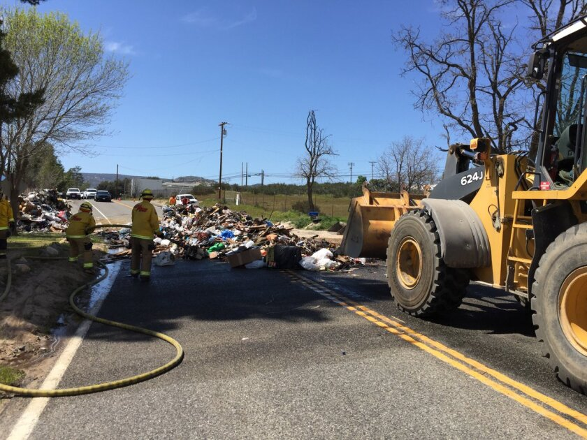 Cal Fire crews work to douse burning trash Tuesday afternoon on state Route 94 near Buckman Springs Road in Campo.