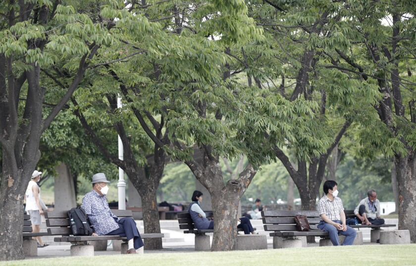 Visitors wearing face masks to prevent the spread of the new coronavirus sit on benches while maintaining social distancing at a park in Seoul, South Korea, Saturday, June 20, 2020. (AP Photo/Lee Jin-man)