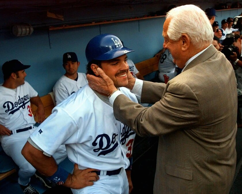 FILE - In this Aug. 15, 1997, file photo, former Los Angeles Dodgers manager and Hall of Famer Tommy Lasorda, right, interacts with Mike Piazza before a ceremony to retire Lasorda's No. 2 jersey in Los Angeles. While some former athletes take an approach to writing in tomes that can be revealing, e