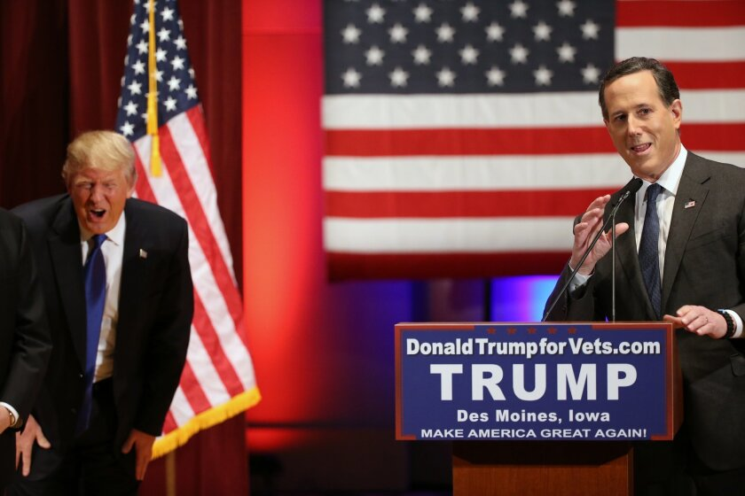 Republican presidential candidate Donald Trump laughs as Republican presidential candidate Rick Santorum jokes about not being photographed in front of a Trump podium sign at a event in support of veterans at Drake University in Des Moines, Iowa, Thursday, Jan. 28, 2016. (AP Photo/Andrew Harnik)