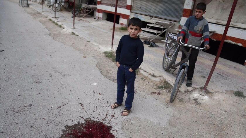 Syrian children stand at the bloodstained site of a shelling Oct. 31 that killed schoolchildren in the rebel-held town of Jisreen, east of the capital, Damascus.