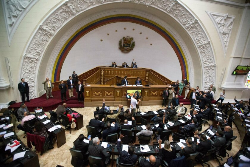 FILE - In this Jan. 6, 2016, file photo, lawmakers vote on the daily agenda during the first National Assembly session in Caracas, Venezuela. The country's attorney general said Saturday, July 30, that the National Assembly is now illegally constituted because in recent days it swore in three membe