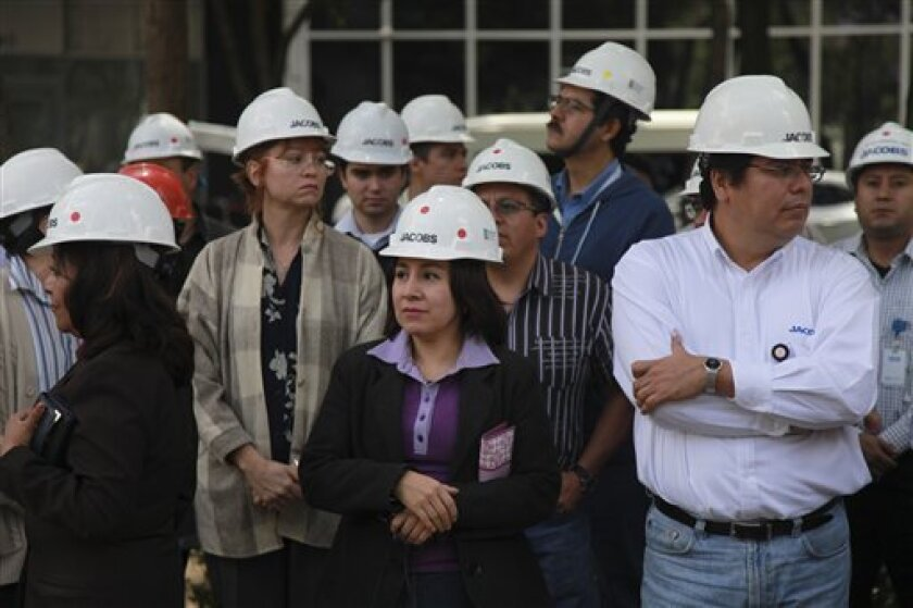 Office workers wearing hard hats stand outside of a building that was evacuated after an earthquake was felt in Mexico City, Mexico, Monday April 2, 2012. Mexico was shaken Monday afternoon by a strong apparent aftershock from a powerful earthquake late last month. Officials said there were no immediate reports of serious damage or injuries from the quake, which had an initial magnitude of 6.3. (AP Photo/Dario Lopez-Mills)