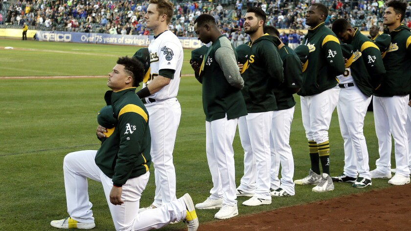 Bruce Maxwell kneels during the national anthem before the start of the A's game against the Rangers on Saturday night in Oakland.