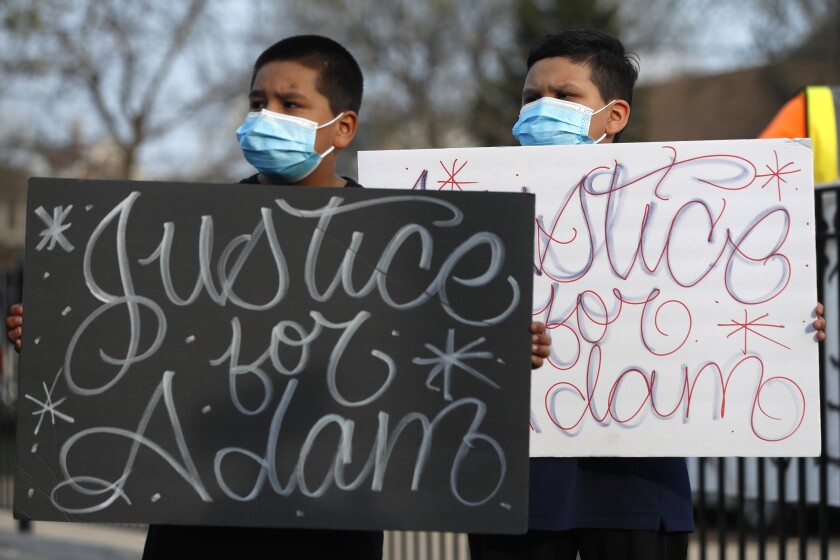 """Two boys hold signs that say """"Justice for Adam."""""""