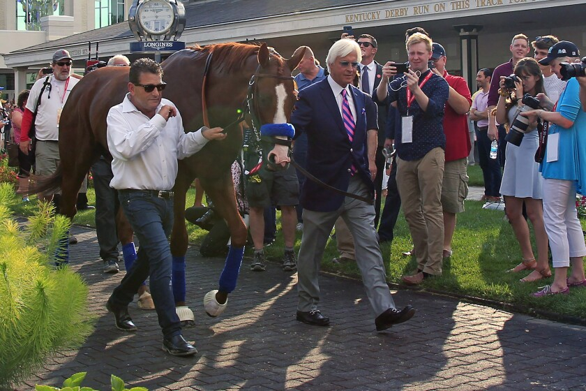 FILE - In this June 16, 2018, file photo, trainer Bob Baffert, right, and assistant Jimmy Barnes, left, lead Triple Crown winner Justify around the paddock at Churchill Downs in Louisville, Ky. Baffert is undefeated taking the Kentucky Derby winner to the Preakness, but for the first time in 20 years he'll do so without assistant trainer Jimmy Barnes, who broke his right wrist in a paddock accident at Churchill Downs. (AP Photo/Garry Jones, File)